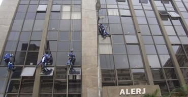 Homens uniformizados realizando a limpeza de fachada predial