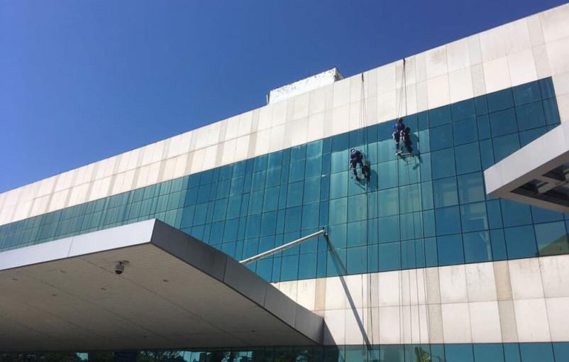 tecnicos em acesso por cordas limpando fachada de prédio